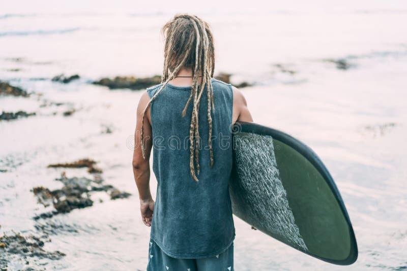 Mann mit Dreadlocks und Surfbrett nahe Ozean lizenzfreie stockbilder