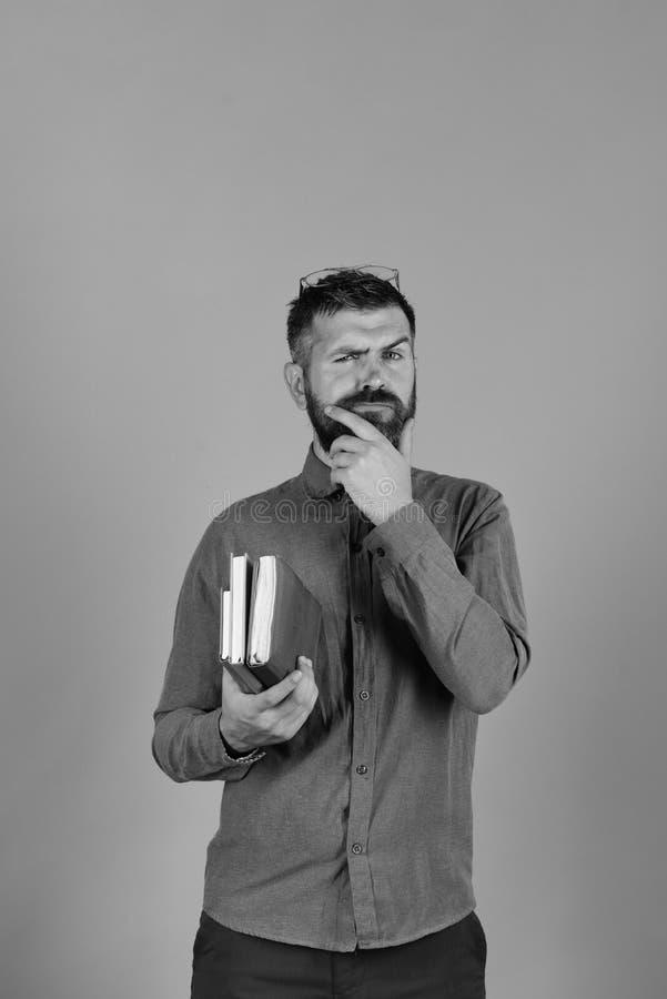 Mann mit durchdachtem Gesicht und Bart hält Stapel von Büchern auf blauem Hintergrund lizenzfreies stockbild