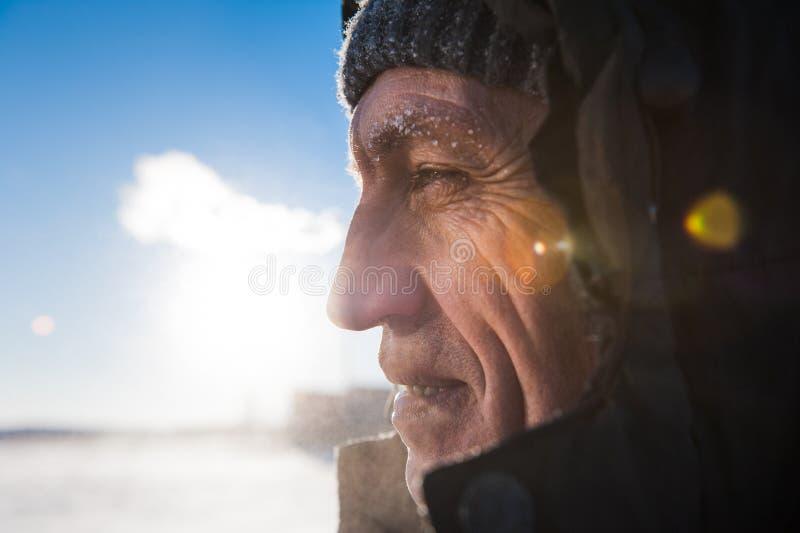 Mann mit einem Bart, der einen polaren Forscher der Kappe trägt, den ein männliches starkes grobes auf dem Hintergrundhimmel mit  stockbilder