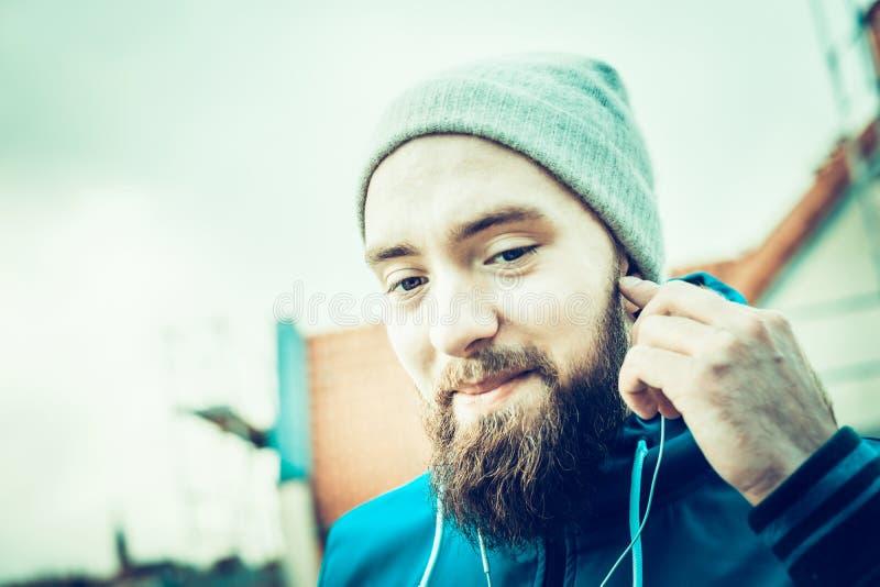 Mann mit einem Bart, einen Hut tragend und mit Kopfhörern lächelnd der städtische Hintergrund verwischte Landschaft lizenzfreie stockbilder