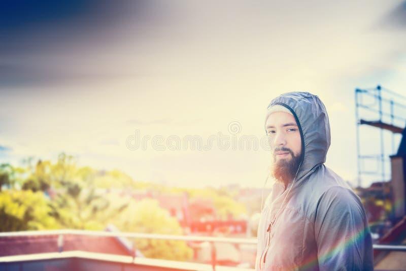 Mann mit einem Bart steht auf Terrasse in Sonnenunterganghintergrundstadtbild stockfoto