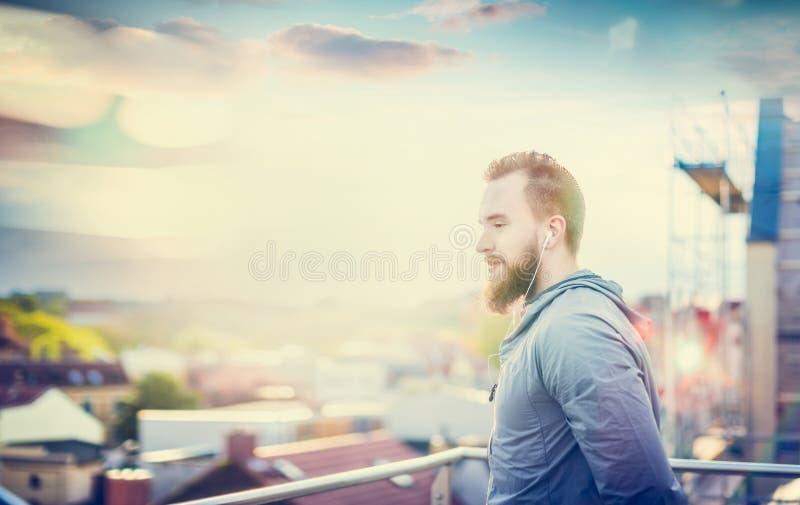 Mann mit einem Bart und einem kurzen Haar, in einer grauen Jacke, stehend auf dem Hintergrund der Stadtlandschaft mit Wolkenunter stockbild