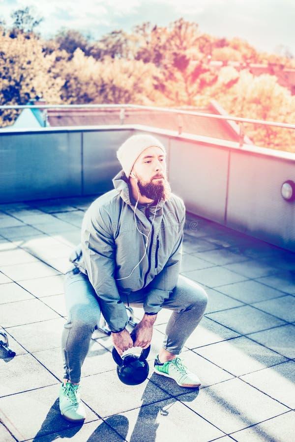 Mann mit einem Barttraining auf der Unterlassungsstadt der Terrasse, tuend hockt mit Gewichten stockfotografie