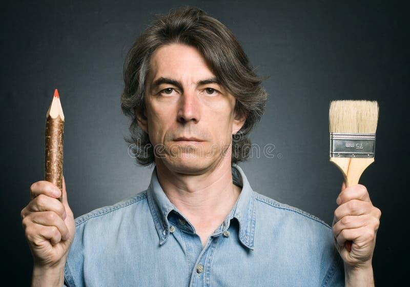 Mann mit einem Bleistift und einem Pinsel stockfoto