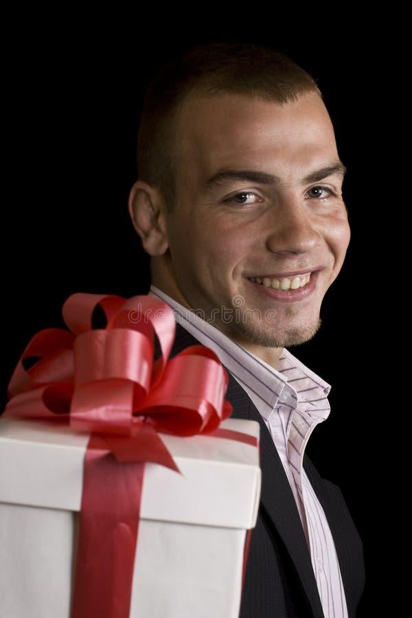 Mann mit einem eingewickelten Geschenkkasten lizenzfreie stockfotos