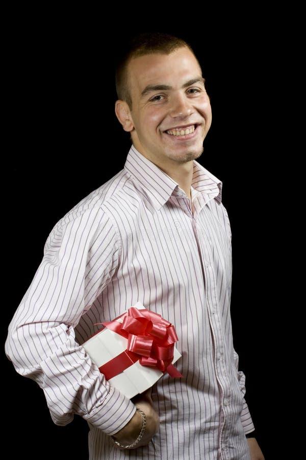 Mann mit einem eingewickelten Geschenkkasten stockbild