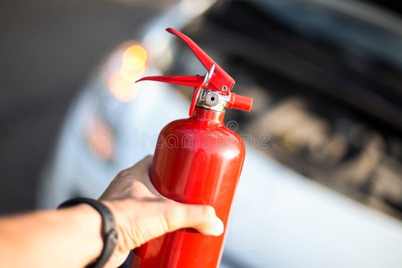Mann mit einem Feuerlöscher in seiner Hand nahe dem Auto stockfotos
