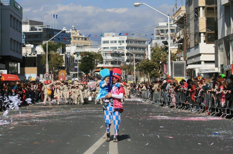 Mann mit einem Kind im Karnevalskostüm gehend entlang eine Straße stockbilder