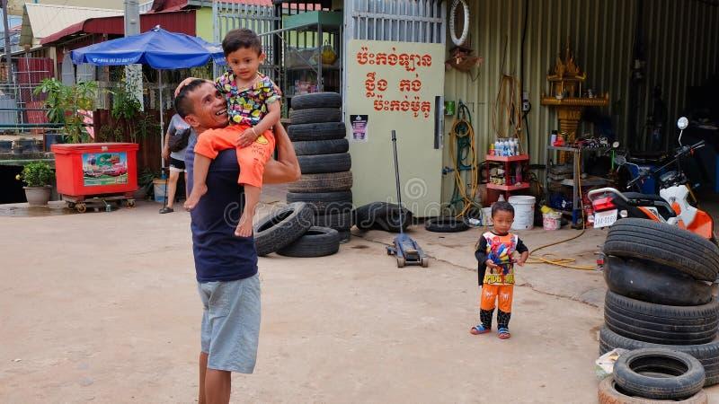Mann mit einem Kind in seinen Armen nahe dem Reifengeschäft, Elendsviertel von Asien, Bewohner von schlechten Bereichen von lizenzfreie stockbilder
