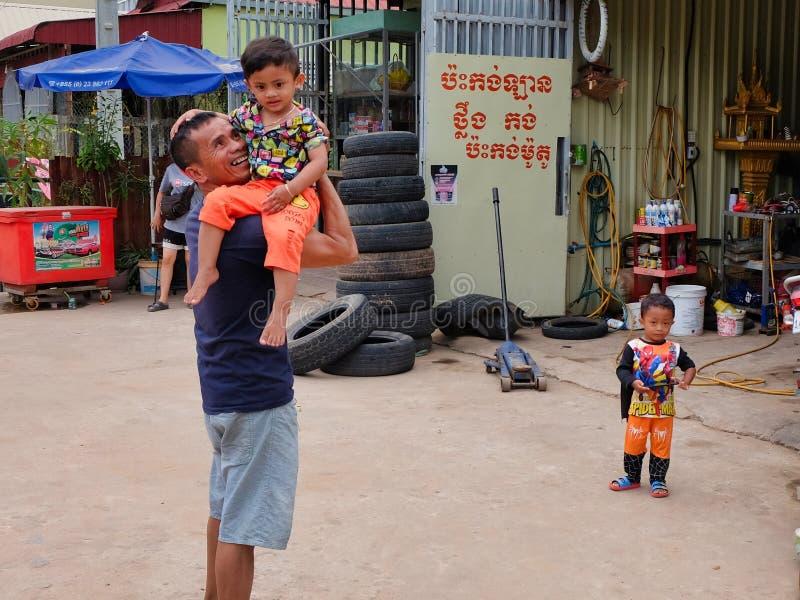 Mann mit einem Kind in seinen Armen nahe dem Reifengeschäft, Elendsviertel von Asien, Bewohner von schlechten Bereichen von stockbild