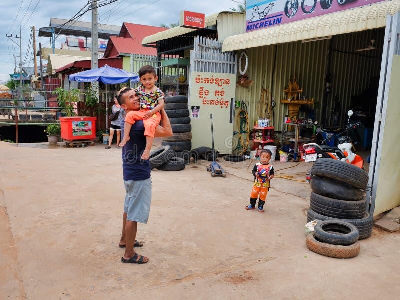 Mann mit einem Kind in seinen Armen nahe dem Reifengeschäft, Elendsviertel von Asien, Bewohner von schlechten Bereichen von lizenzfreie stockfotografie