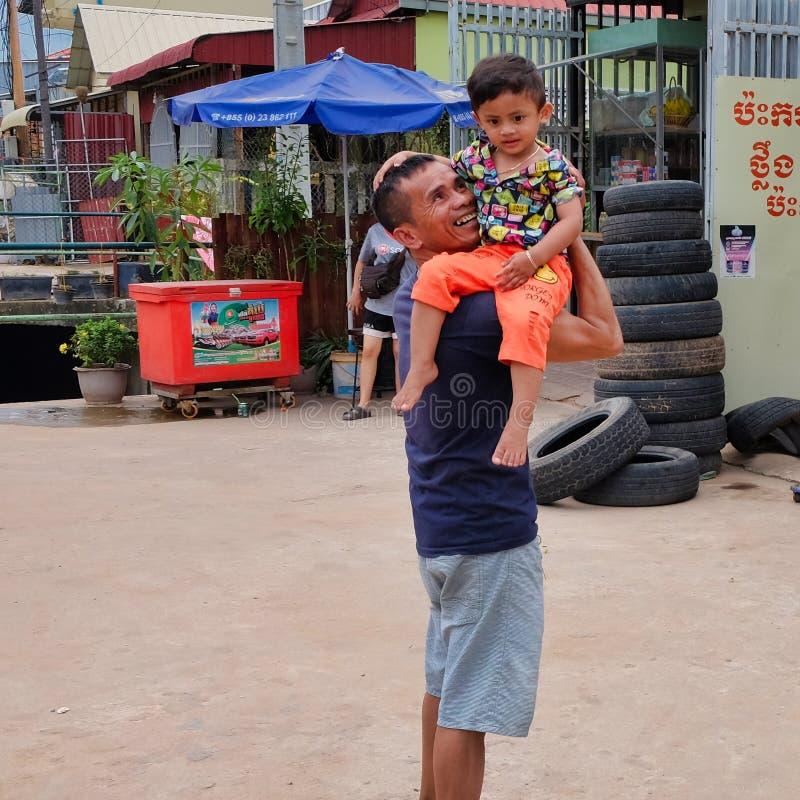 Mann mit einem Kind in seinen Armen nahe dem Reifengeschäft, Elendsviertel von Asien, Bewohner von schlechten Bereichen von stockbilder