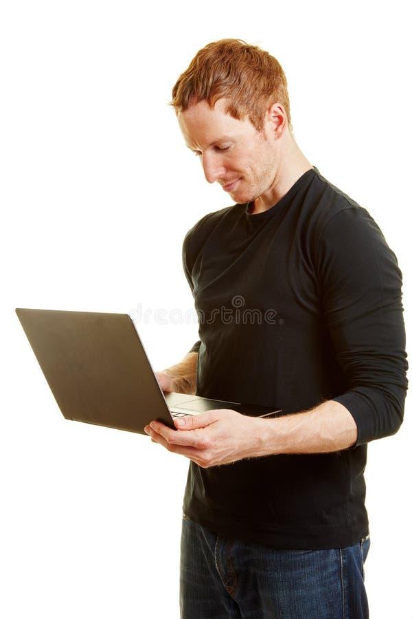 Mann mit einem Laptop als Programmierer stockfotos
