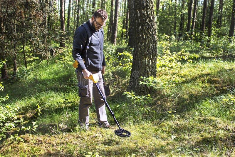 Mann mit einem Rucksack auf seinem hintere Stände im Wald mit einem Metalldetektor in seiner Hand und in Suchen der Bereich auf d stockbild
