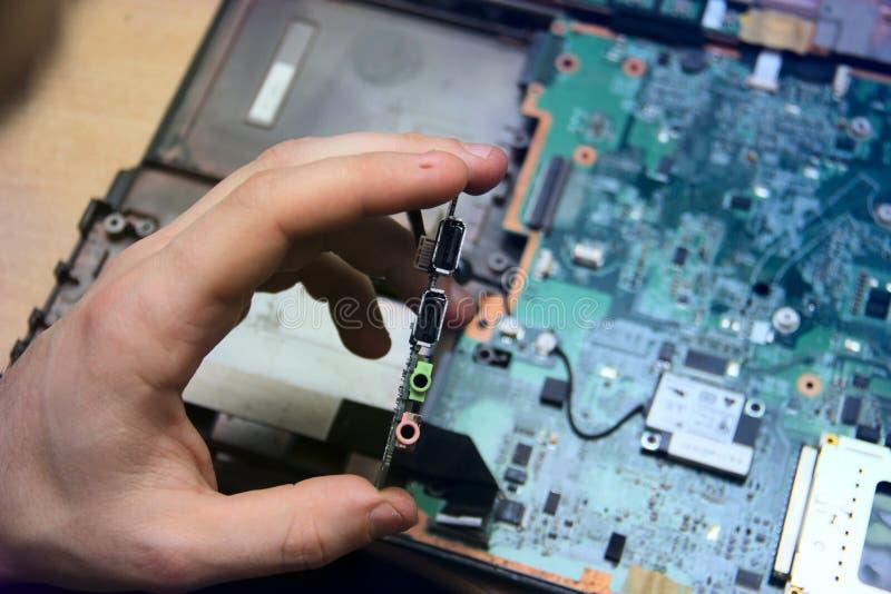 Mann mit einem Schraubenzieher repariert Computerausrüstung ausführlich seine Hände und des Gerätes der Norden, Süd, Brücke des M lizenzfreie stockbilder