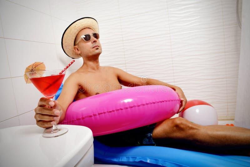 Mann mit einem Schwimmenring, der im Badezimmer sich entspannt stockfoto