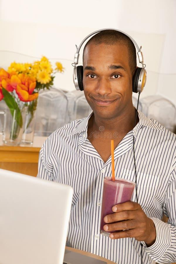 Mann mit einem Smoothie und einem Laptop lizenzfreies stockfoto
