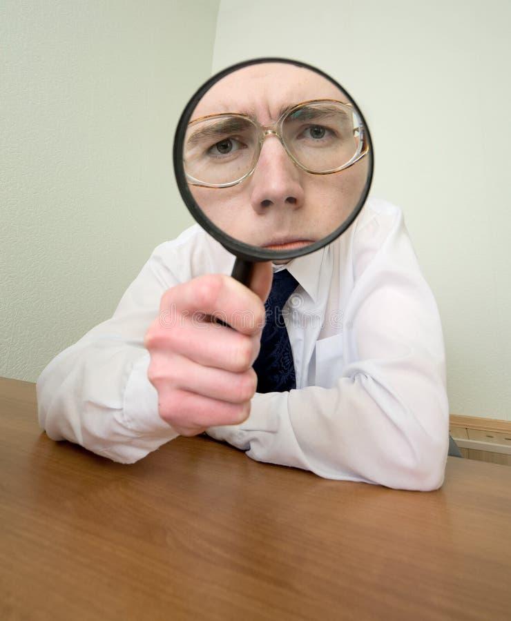 Mann mit einem Vergrößerungsglas in einer Hand lizenzfreie stockfotos