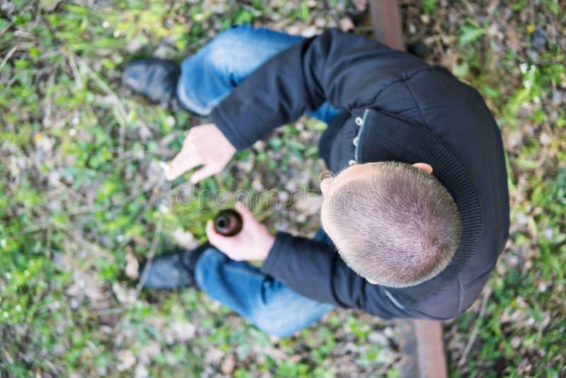Mann mit einer Flasche und einer Zigarette lizenzfreies stockbild