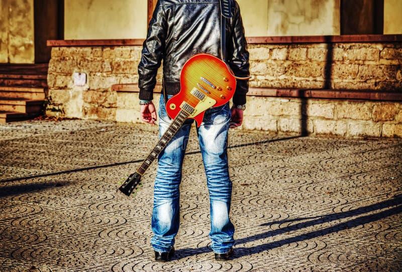 Mann mit einer Gitarre auf seiner Schulter stockbild