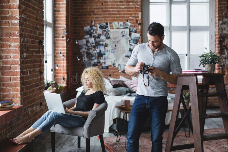 Mann mit einer Kamera gekleidet in einem grauen T-Shirt und in einer Frau in einem schwarzen T-Shirt mit einem Laptop lizenzfreie stockfotos
