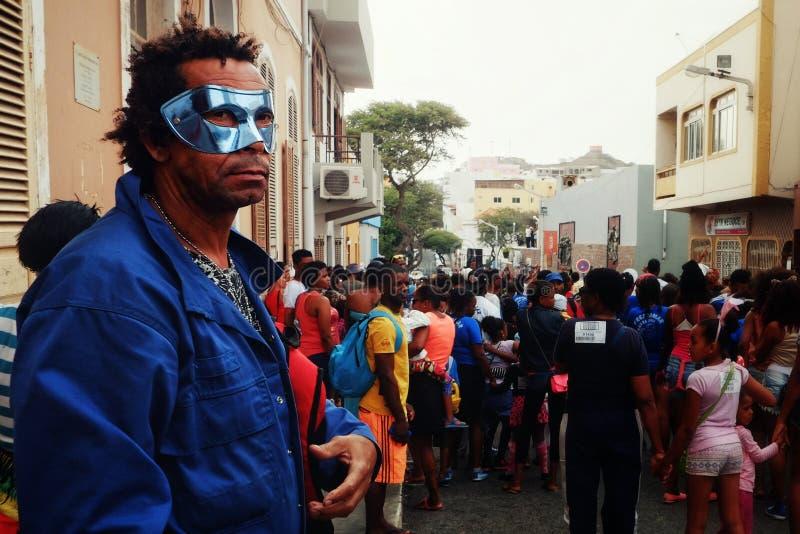 Mann mit einer Maske das Karnevalsereignis auf den Straßen der Stadt aufpassend lizenzfreies stockbild