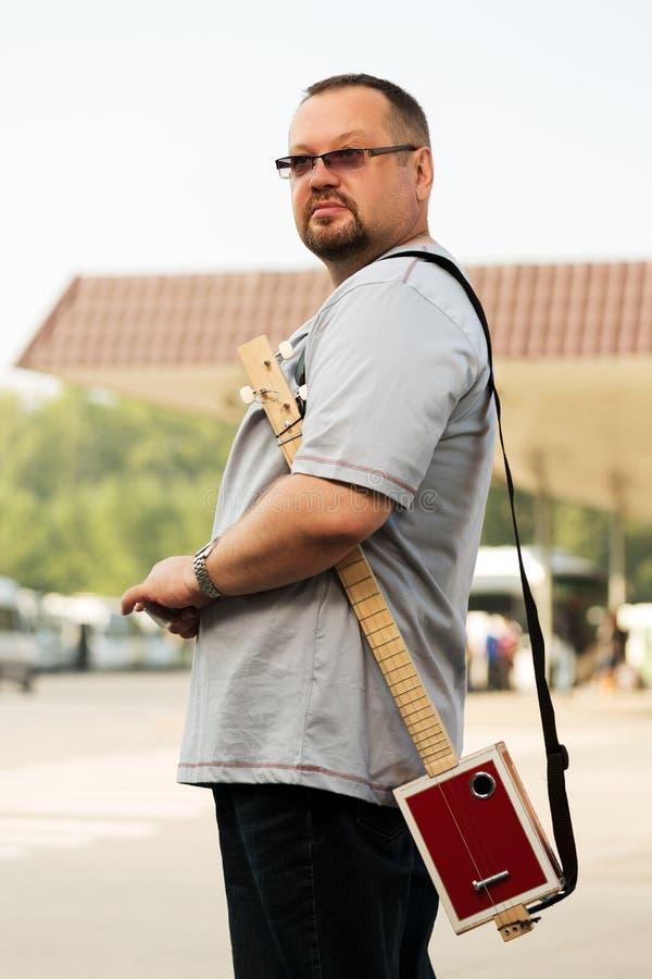 Mann mit einer Zigarrenschachtelgitarre mit drei Schnüren lizenzfreie stockbilder