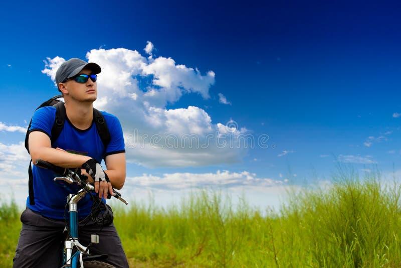 Mann mit Fahrrad auf grünem Feld stockbilder