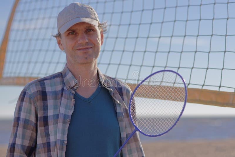 Mann mit Federballschläger auf einem Strand lizenzfreie stockbilder