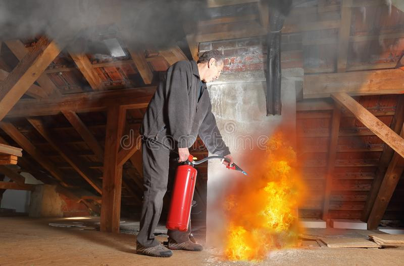 Mann mit Feuerlöscher kämpfendem agains Feuer in seinem Haus stockfoto