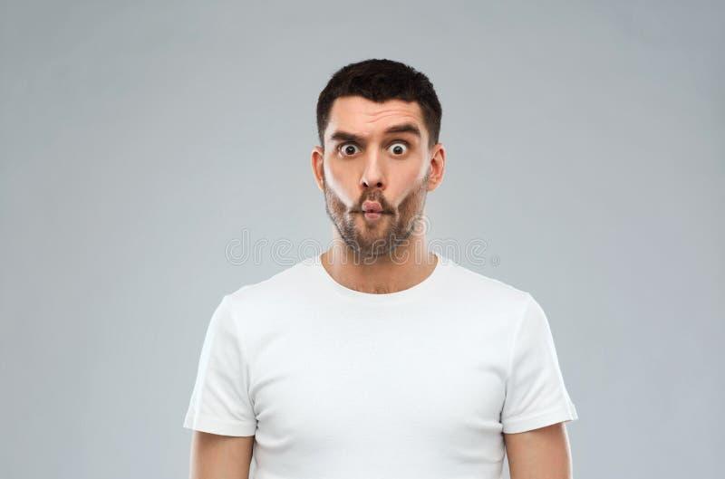 Mann mit Fischgesicht über grauem Hintergrund stockfotos