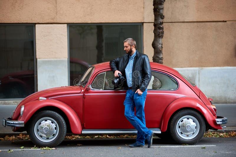 Download Mann Mit Fotokamera Nahe Rotem Retro- Auto Stockfoto - Bild von luxus, draußen: 106803160