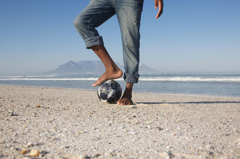 Mann mit Fuß auf Fußball am Strand lizenzfreie stockfotos