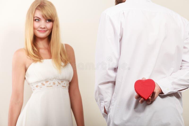 Mann mit geformter Geschenkbox des Herzens für Frau stockfoto
