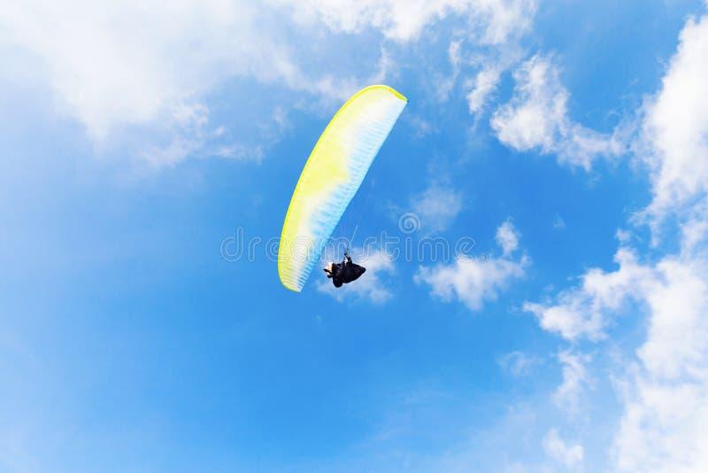 Mann mit gelbem Fallschirm über blauem Himmel lizenzfreies stockbild