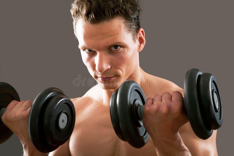 Mann mit GewichtsAusbildungsanlageen stockfotografie