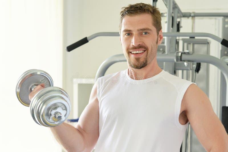 Mann mit GewichtsAusbildungsanlageen lizenzfreie stockfotos