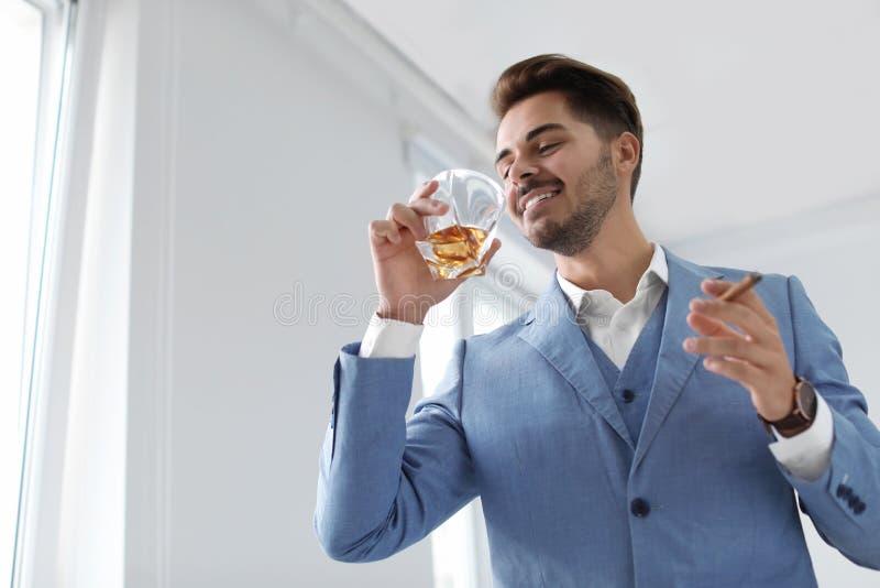 Mann mit Glas des Whiskys und der Zigarre lizenzfreie stockfotos