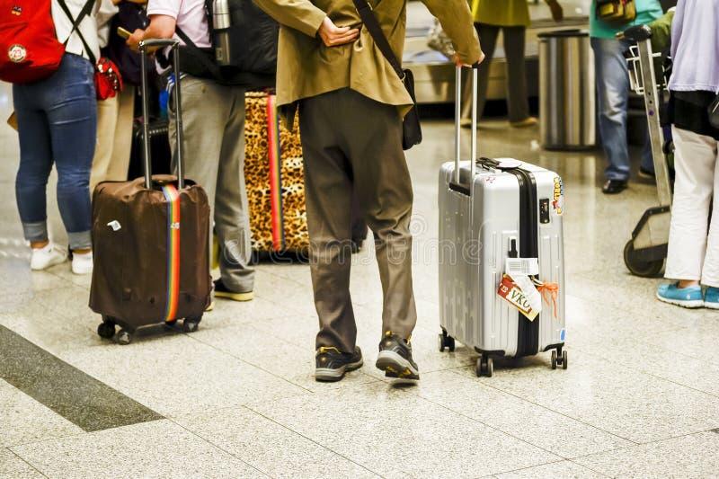 Mann mit großem silbernem Koffer am Flughafen von Russland, Moskau, Flughafen Vnukovo, im Juni 2017 blurry lizenzfreie stockfotos