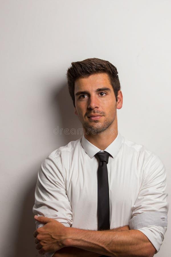 Mann mit Hemd und Bindung, die an einer Wand mit den gekreuzten Armen sich lehnt stockfotografie