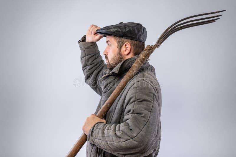 Mann mit Heugabel auf seiner Schulter gibt die Grußgeste, gekleidet in altmodischer Kleidung - Kappe und Wolle-aufgefüllte Jacke  lizenzfreies stockbild