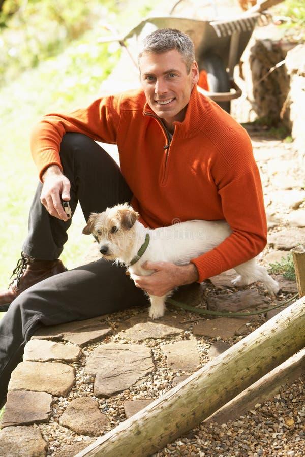 Mann mit Hund auf Bruch von der Gartenarbeit stockbilder