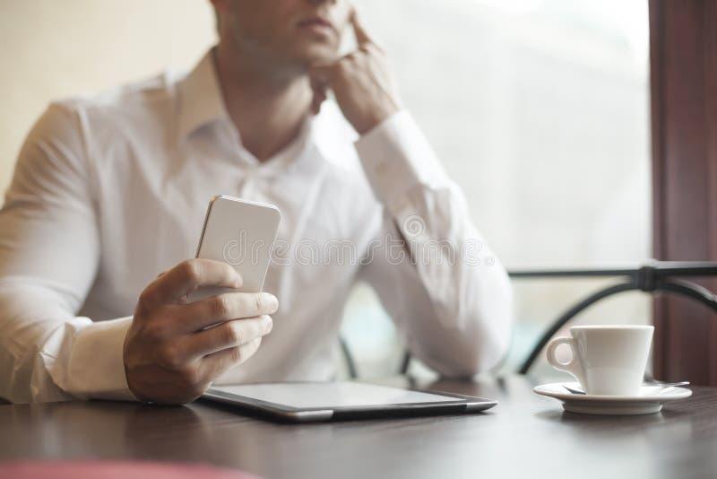 Geschäftsmann mit smartphone im Café stockfotografie