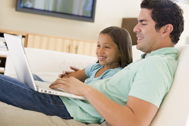 Mann mit jungem Mädchen im Wohnzimmer mit Laptop stockfotografie