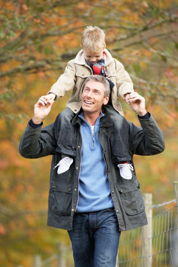 Mann mit jungem Sohn auf Schultern im Herbst-Park stockfoto