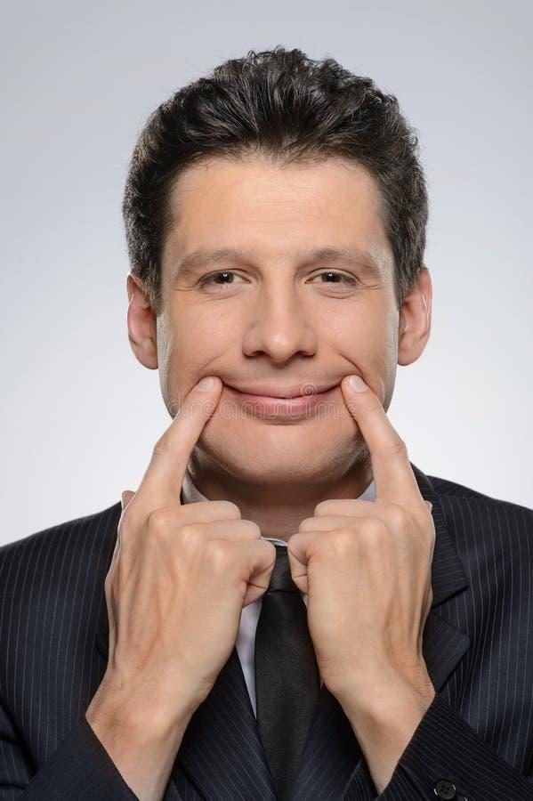 Mann mit künstlichem Lächeln. Geschäftsmann, der ein Gesicht an Kamera h macht stockbilder