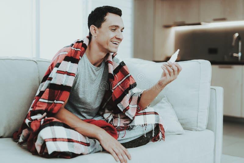 Mann mit kaltem Sitzen auf Sofa in der karierten Decke Mann zu Hause Kranker junger Mann Weißes Sofa im Raum Krankheitskonzept Ge stockfotos