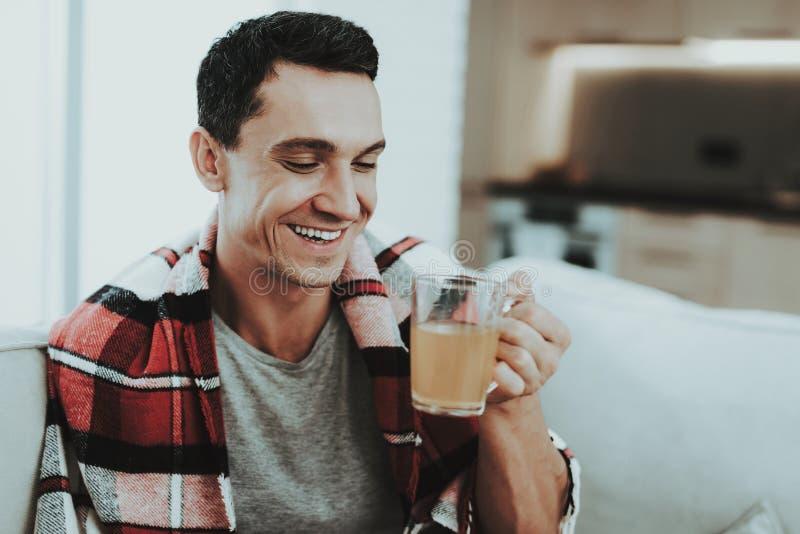 Mann mit kaltem Sitzen auf Sofa in der karierten Decke Mann zu Hause Kranker junger Mann Weißes Sofa im Raum Lächelnder Kerl Kran stockbild