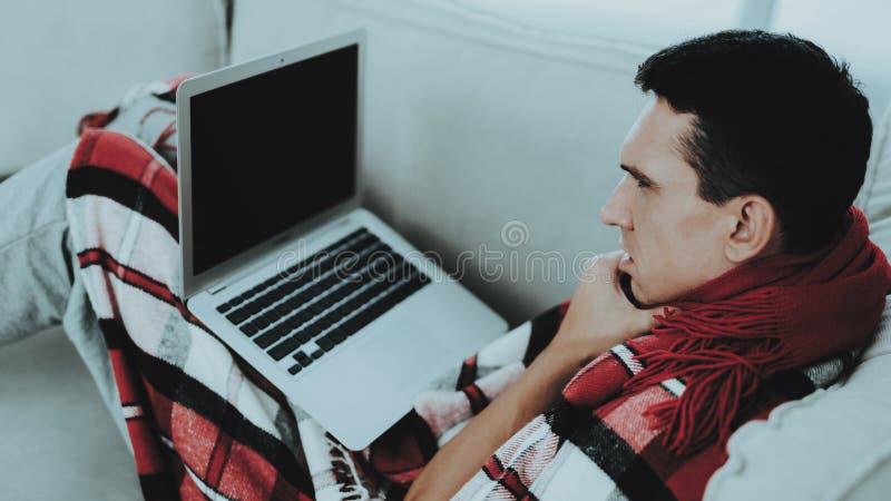 Mann mit kaltem Sitzen auf Sofa in der karierten Decke Mann zu Hause Kranker junger Mann Weißes Sofa im Raum Unglücklicher Kerl K stockbilder