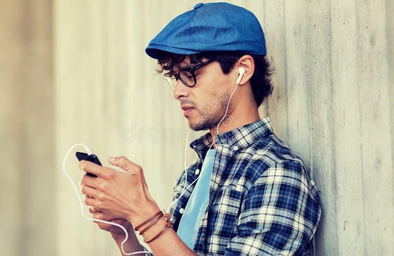 Mann mit Kopfh?rern und h?render Musik des Smartphone stockfoto
